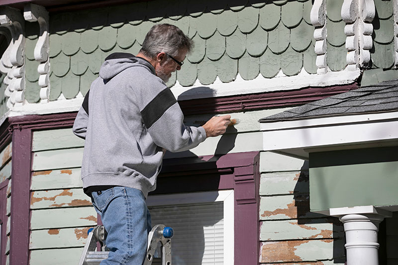 man on stepladder painting exterior siding on victorian house
